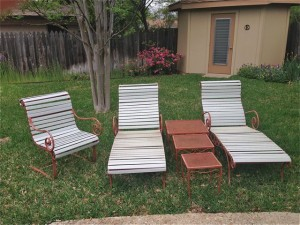 Vintage Woodard chaise loungers with wrought iron tables.